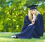 A beautiful graduate sitting on the lawn