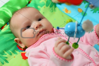 Baby playing on a colorful blanket