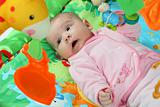 Little baby playing on a colorful jungle blanket