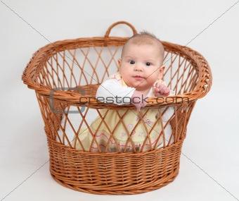 Little baby girl sitting in basket