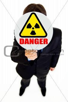 Ð¡oncept-radiation danger! Businessman holding  radiation sign in front of face