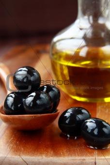 black olives and Olive Oil on an old tablel