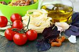 Italian Pasta with tomatoes, olive oil and basil on wooden background