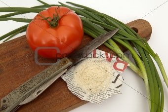 Tomato, salt on the newspaper, a knife and an onions on a board