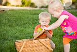 Cute Brother and Sister Toddlers Playing with Apple and Picnic Basket in the Park.