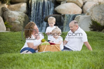 Happy Adorable Young Family with Twins Enjoy a Picnic in the Park.