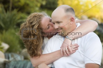 Happy, Attractive, Affectionate Couple Kiss on Cheek in the Park.