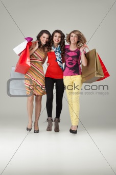 studio image three beautiful young women holding shopping bags