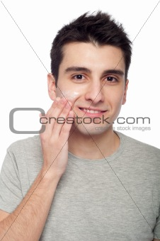 Young man applying cream lotion