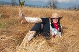 Woman cowboy relax on the straw in a field