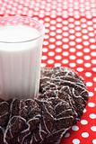 A glass of milk and tasty cookies on a white plate