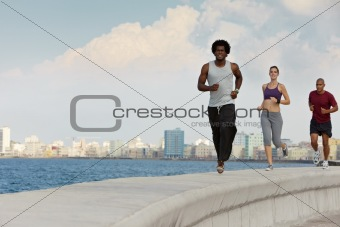 three friends doing sport activities near the sea