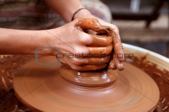 clay potter hands closeup working on wheel handcrafts