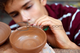 boy teen potter clay bowl working in pottery workshop