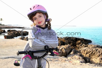 bicycle little happy girl pink helmet in rocky sea