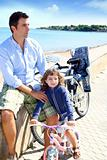 daughter and father on bicycle in beach sea