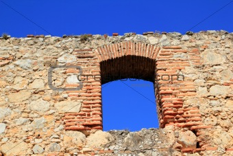 brick segmental arch in ancient masonry stone wall