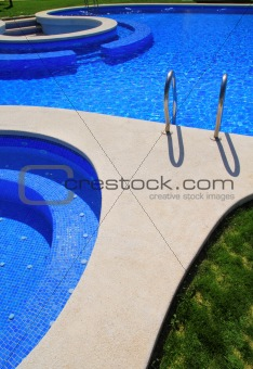 blue tiles swimming pool with green grass garden