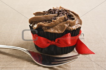 Cup cake with red bow and fork