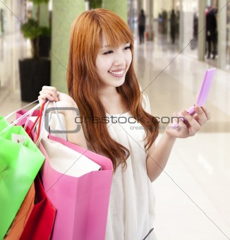 young woman holding mobile phone and shopping bag in the mall