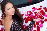 Young pretty woman with a New car in red rose petals