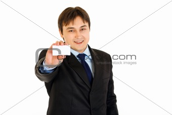 Smiling modern businessman holding blank business card