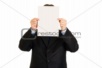 Businessman holding white paper in front of his face
