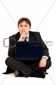 Sitting with laptop on floor businessman holding finger at mouth. Shh gesture