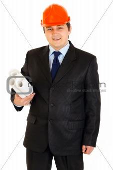 Smiling businessman in helmet holding building plans in hand