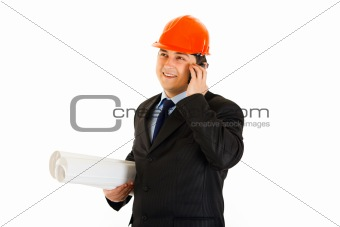 Smiling businessman in helmet holding building plans and talking on mobile