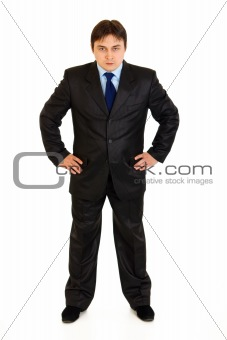 Full length portrait of strict businessman with hands on hips attentively looking at you
