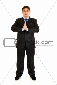 Full length portrait of praying businessman with closed eyes