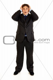 Full length portrait of shocked businessman holding hands near head and looking up