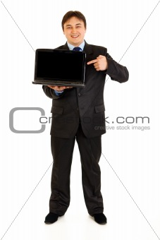 Full length portrait of smiling modern businessman pointing finger on laptops blank screen