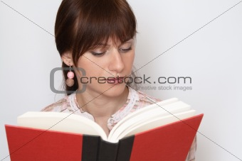 Young beautiful brunette reading a red book