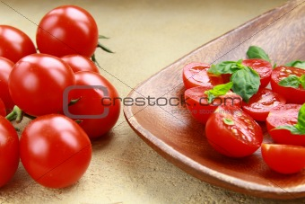 Tomatoes Cherry fresh ripe whole and sliced ​​on a plate