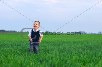A beautiful little boy staing in the grass