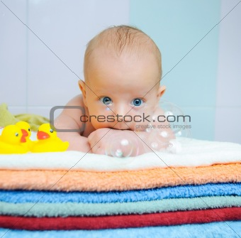 Little cute boy with soap bubbles lying on colorful towels