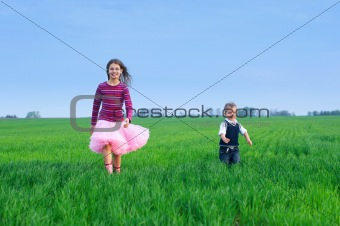 sister runing with her brather on the grass