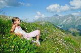 girl lying in a meadow backround Alps