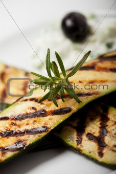 grilled zucchini with a rosemary leaf