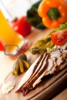 slices of cold roast pork on a wooden plate