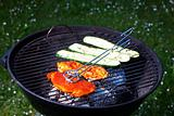 pork steak and zucchini on a grill outdoors