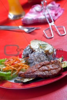 grilled pork steak on a plate outdoors