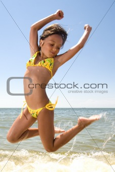 Little girl jumping at the sea
