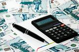 Calculator notebook and pen on a background the Russian roubles.