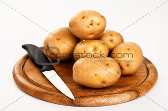 Ceramic knife and fresh appetizing potato on a cutting board.