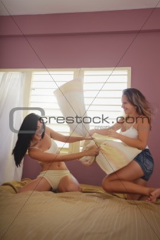 yound adult women fighting with pillows