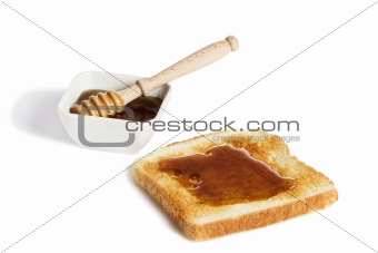 toast with honey an a honey jar with a honey dipper