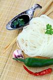 Asian glass noodles, chili pepper and soy sauce on bamboo mat